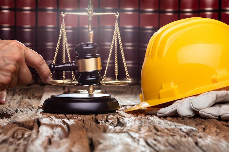 Judge Striking Gavel In Front Of Yellow Safety Helmet On The Wooden Table
